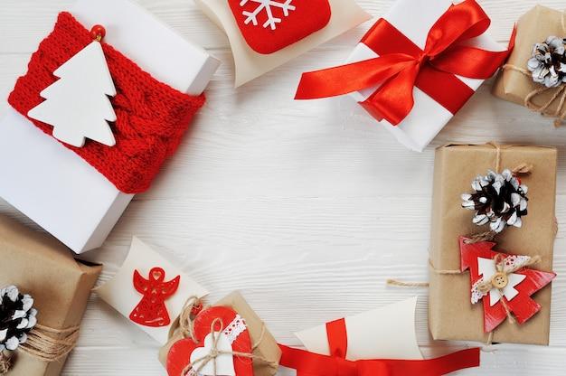 Prezenty świąteczne pudełka ozdobione czerwonymi kokardkami są ułożone w okrąg na białym drewnianym tle.