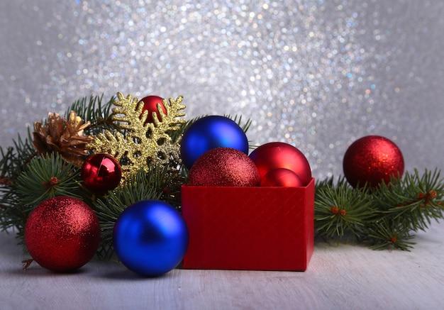 Prezenty świąteczne. świąteczne dekoracje z prezentami i czerwoną piłkę z gałęzi jodłowych