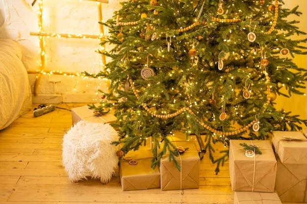 Prezenty świąteczne w papierze rzemieślniczym z żółtymi, różowymi i białymi wstążkami, sosnowymi gałązkami i girlandą