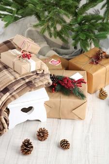 Prezenty świąteczne w pobliżu choinki na drewnianej powierzchni