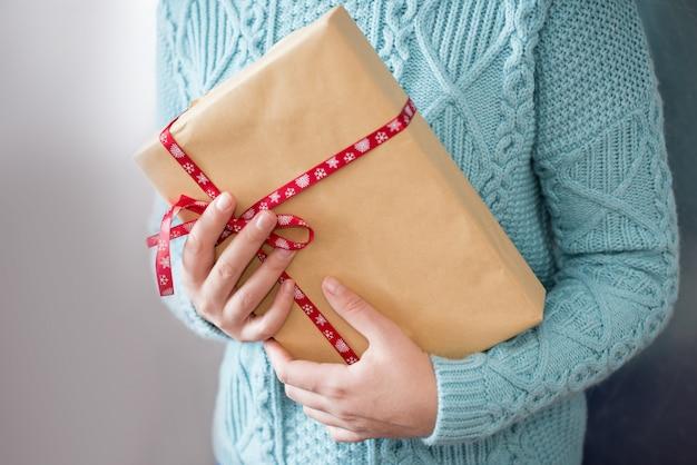 Prezenty świąteczne. wesołych świąt. rękawiczki z dzianiny. dzianinowa sukienka. pudełko z prezentami prezent
