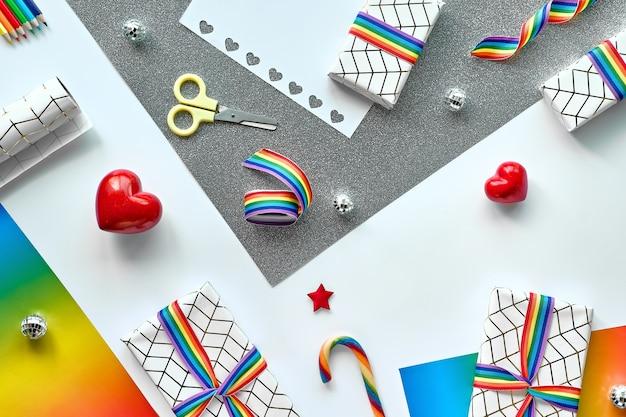 Prezenty świąteczne z tęczową wstążką w kolorach flagi społeczności lgbtq i dekoracjami świątecznymi.