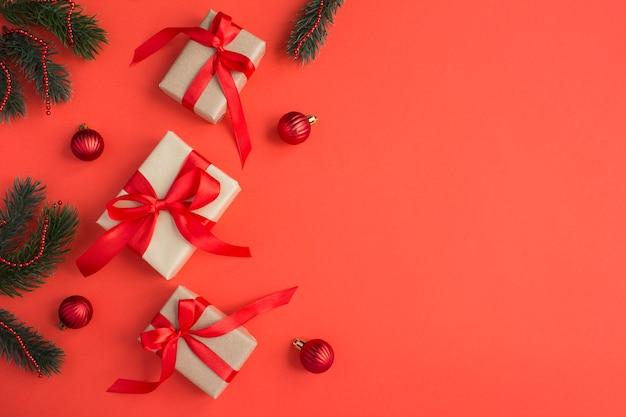 Prezenty świąteczne z tiew czerwoną kokardą na czerwonym tle. skopiuj miejsce.