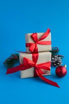 Prezenty świąteczne z wiązaną czerwoną kokardą na niebieskim tle. zbliżenie.