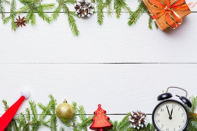 Prezenty świąteczne, zabawki, vintage zegar i czapka mikołaja na drewnianym białym