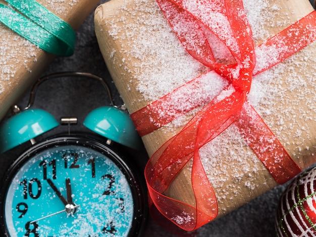 Prezenty świąteczne ze wstążkami i śniegiem. zegar