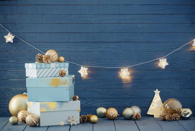 Prezenty świąteczne ze złotymi dekoracjami na niebieskim tle drewnianych