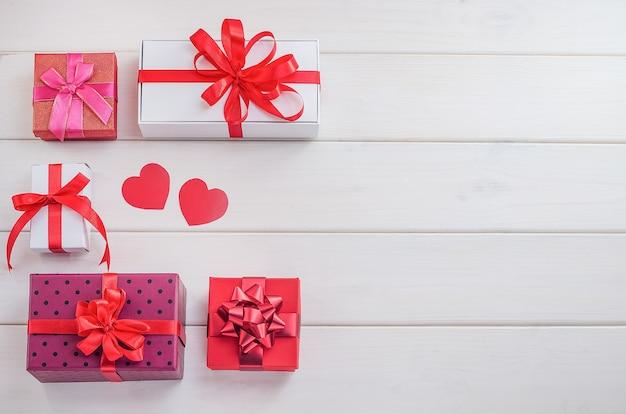 Prezenty, tła na walentynki, dzień matki. wielokolorowe pudełka na prezenty z czerwonymi wstążkami i sercami na białym tle drewniane z miejsca na kopię. świąteczna wyprzedaż, gratulacje.