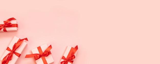 Prezenty urodzinowe niespodzianka z czerwoną kokardą na różowym tle. leżał płasko, widok z góry, miejsce.