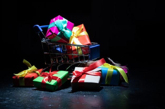 Prezenty w kolorowych pudełkach w koszyku. zbliżenie