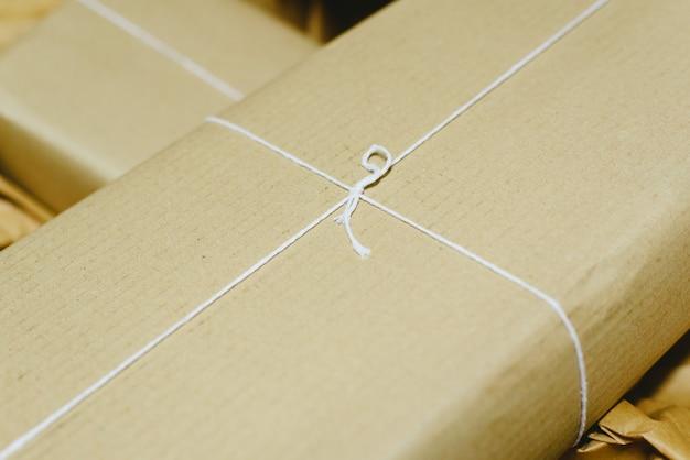 Prezenty w prostych kartonowych pudełkach z białym sznurkiem