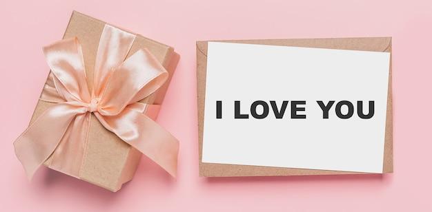 Prezenty z listem nutowym na na białym tle różowym tle, koncepcja miłości i walentynki z tekstem kocham cię