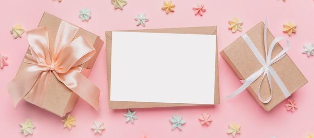 Prezenty z listem uwagę na na białym tle różowej powierzchni ze słodyczami