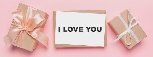 Prezenty z notatką na na białym tle różowym tle, koncepcja miłości i walentynki z tekstem kocham cię