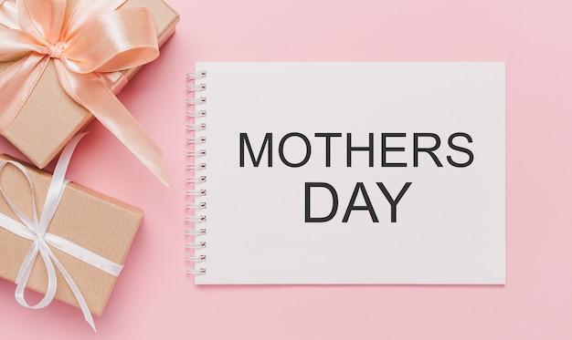 Prezenty z notatką na na białym tle różowym tle, miłość i koncepcja walentynki z tekstem dzień matki