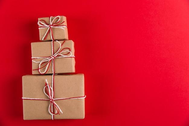 Prezenty z papieru rzemieślniczego i lin w kształcie choinki na czerwonym, świątecznym, z życzeniami copyspace.