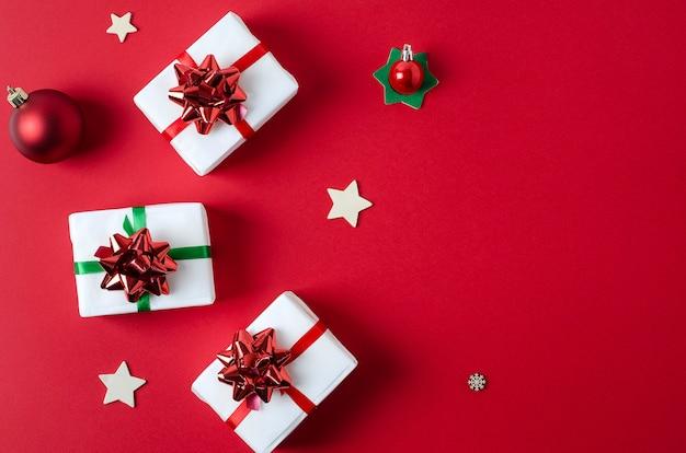 Prezenty zapakowane w biały papier przewiązane czerwonymi i zielonymi wstążkami leżą na jasnoczerwonym, pionowym tle z miejscem na kopię