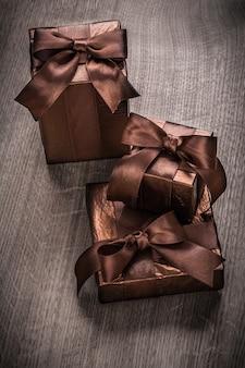 Prezenty zapakowane w brokatowy papier z brązowymi wstążkami w wersji pionowej