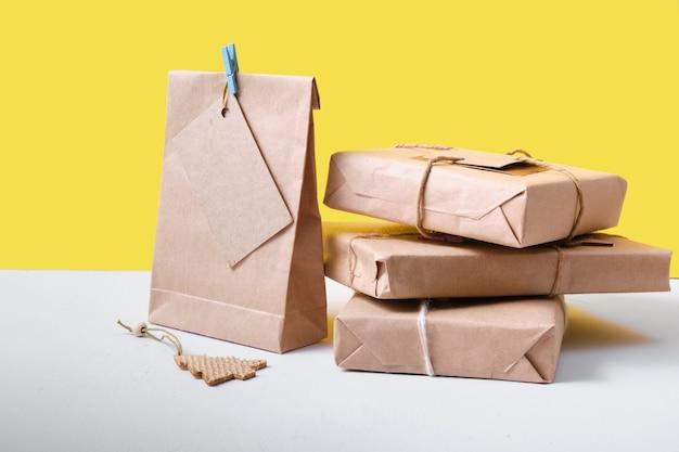 Prezenty zapakowane w eko papier na żółtym tle, koncepcja stylu życia zero waste, opakowania na prezenty diy
