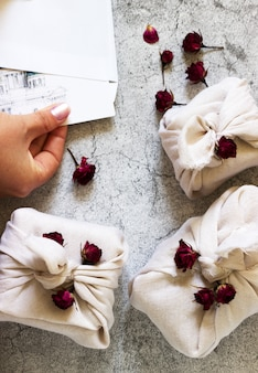 Prezenty zapakowane w furoshiki, suszone róże i dłonie dostające pocztówkę z koperty na szaro