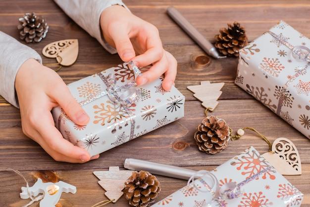 Prezenty zawinięte w świąteczny papier w rękach dzieci i ozdoby świąteczne na drewnianym tle. przygotowania świąteczne