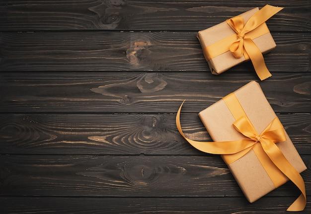 Prezenty związane ze złotą wstążką na drewniane tła