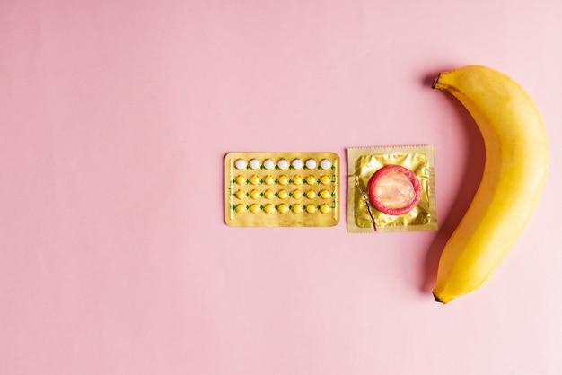 Prezerwatywa na opakowaniu, banan i pigułka antykoncepcyjna