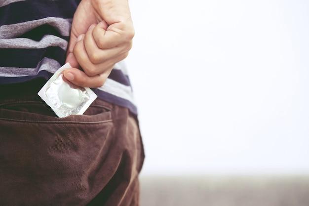 Prezerwatywy gotowe do użycia w kobiecej dłoni, zapewniają kondom bezpieczny seks na łóżku zapobiegają infekcjom, a środki antykoncepcyjne kontrolują wskaźnik urodzeń lub bezpieczną profilaktykę. światowy dzień walki z aids, zostaw miejsce na tekst.