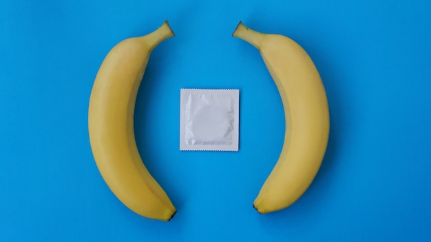 Prezerwatywy i dwa banany razem na niebieskim tle, koncepcja środków antykoncepcyjnych i profilaktyki chorób wenerycznych małżeństw osób tej samej płci.