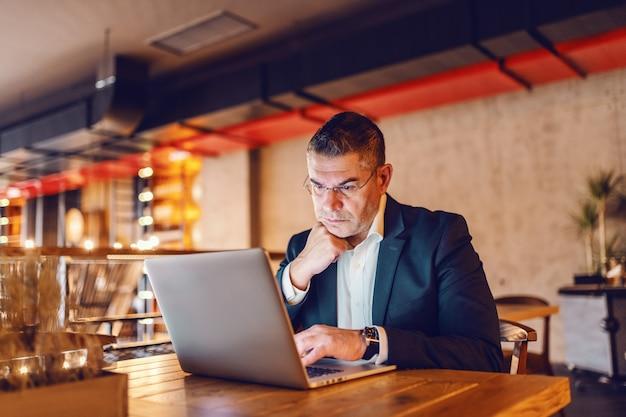 Prezes korzysta z laptopa siedząc w stołówce.