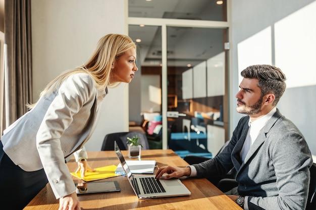 Prezes stoi w biurze i kłóci się ze swoim pracownikiem. mężczyzna siedzi przy biurowym stole przed laptopem i przyjmuje krytykę. problemy w pracy