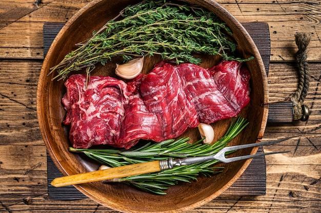 Prime raw maczeta spódnica stek wołowy w drewnianym talerzu z ziołami