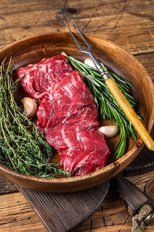 Prime raw stek wołowy ze spódnicą maczety na drewnianym talerzu z ziołami. drewniane tła. widok z góry.