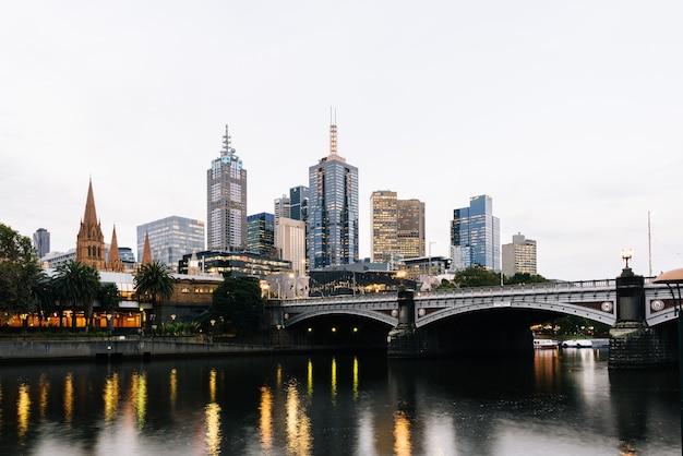 Princes bridge i budynki miejskie nad rzeką yarra w melbourne, australia wieczorem - 2021