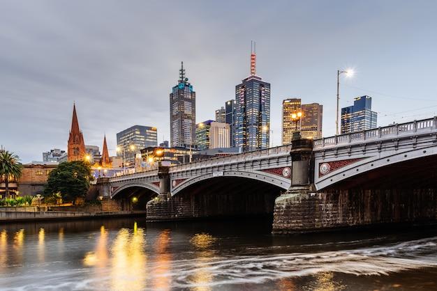 Princes bridge i budynki miejskie nad rzeką yarra w melbourne, australia wieczorem