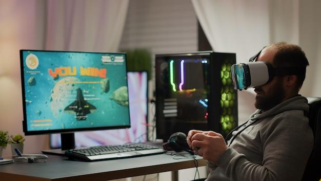 Pro cyber-sportowy gracz wygrywający gry wideo za pomocą zestawu słuchawkowego vr. mistrzostwa w wirtualnej strzelance kosmicznej w cyberprzestrzeni, gracz e-sportowy występujący na potężnym komputerze podczas turnieju gier