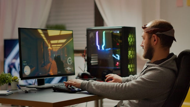 Pro esport man gamer uśmiecha się do kamery grając w gry wideo pierwszoosobowe strzelanki na wirtualnych mistrzostwach. cyber przesyłanie strumieniowe online na potężnym komputerze osobistym podczas turnieju