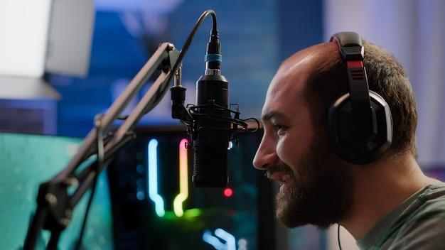Pro streamer siedzący na fotelu do gier, rozmawiający z graczami za pomocą profesjonalnego mikrofonu, grający w kosmiczną strzelankę podczas turnieju online. cyberman rozmawia na czacie strumieniowym