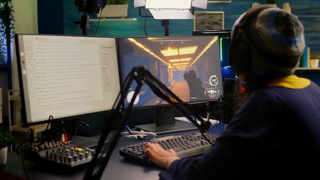 Pro streamer sprawdza dźwięk na mikserze i zaczyna grać w strzelankę pierwszoosobową podczas wirtualnych zawodów