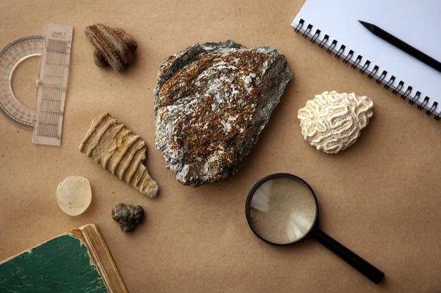 Próbka kamienia z pętlą i notatnikiem w laboratorium geologicznym. analiza skał materiałów i gleb
