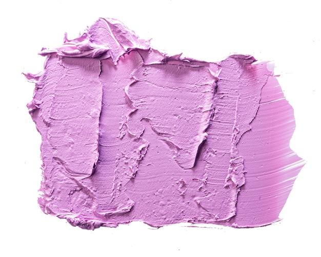 Próbka korektora kosmetycznego koloru fioletowego na białym tle