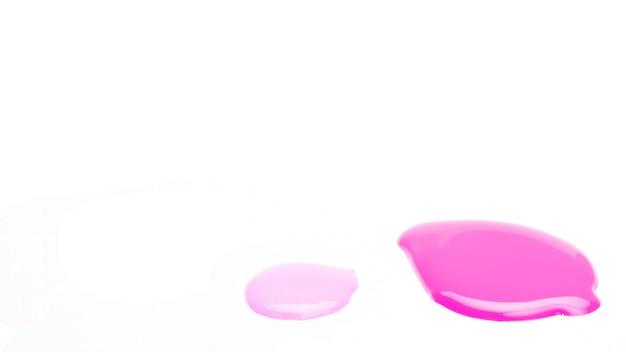 Próbka kropli lakieru do paznokci na białej powierzchni