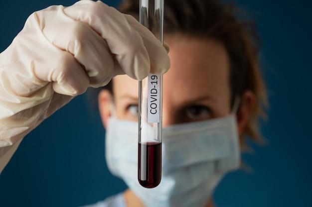 Próbka krwi w szklanej probówce z etykietą covid 19
