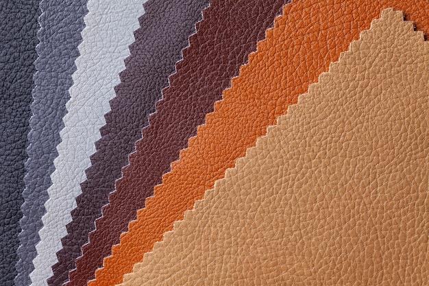 Próbka tkaniny skórzanej w kolorze brązowym i szarym, tło. katalog i ton palety tkanin wewnętrznych na meble, zbliżenie.