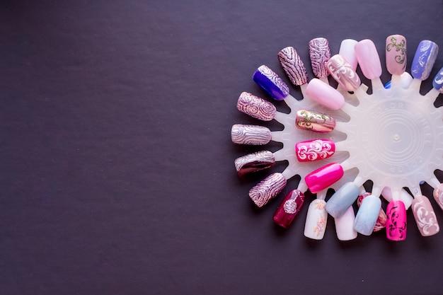 Próbki różnych wzorów pomalowanych paznokci na szarym tle