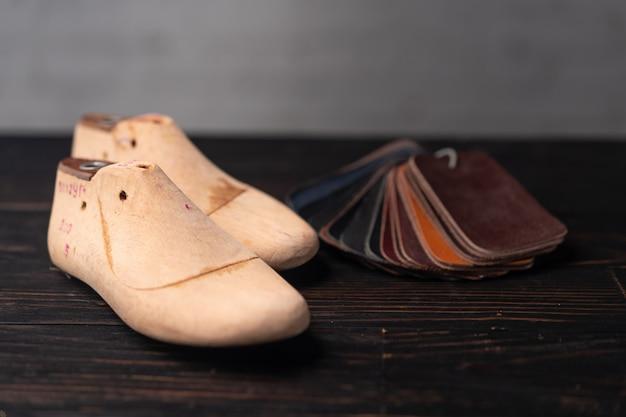 Próbki skóry do obuwia i buta z tworzywa sztucznego wytrzymują na ciemnym drewnianym stole
