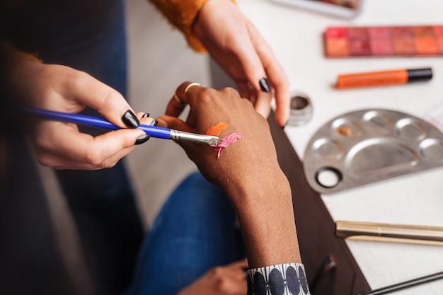 Próbki szminki. ciemnoskóra kobieta nosząca pierścionki próbująca nowych próbek szminek