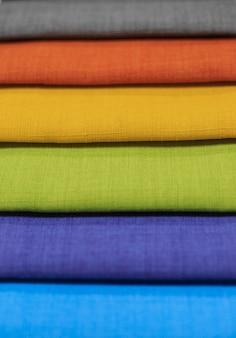 Próbki tkanin. próbki tkanin na zasłony. wiszące próbki żółtej, niebieskiej, pomarańczowej, zielonej tonacji.