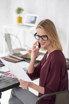 Problem biznesowy. widok z góry wesoła ładna bizneswoman pozuje przy stole i przy użyciu telefonu