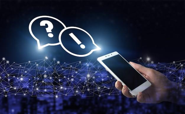Problem, potrzeba pomocy i porady. ręka trzymać biały smartfon z cyfrowym hologramem znak zapytania na ciemnym tle miasta niewyraźne. faq concept image.znajdź odpowiedź online.